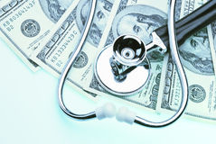 Healthcare cost. Money and stethoscope to illustrate the cost of health care Royalty Free Stock Photos