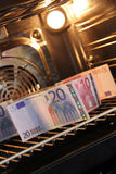 Money in the stove Royalty Free Stock Image