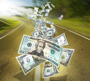 Money stream. An exploding US money stream flying down a golden asphalt road.  Blurred background to depict movement.  Concept for receiving or getting money Royalty Free Stock Images