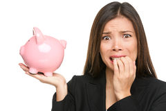 Money stress - business woman holding piggy bank. Debt, bankruptcy and savings concepts with stressed female businesswoman biting nails nervous isolated Royalty Free Stock Image