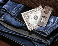 Money and a suitcase with jeans Stock Image