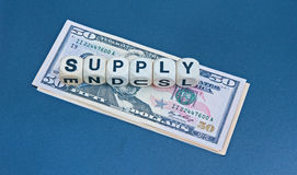 Money supply. Text ' Supply ' in black upper case letters on small white cubes placed upon a pile of United States Dollar bills isolated on a  blue background Royalty Free Stock Images