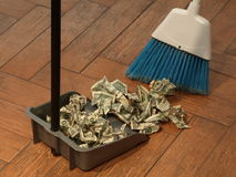 Money sweep 10. Photo of  a broom and dust pan sweeping up money Royalty Free Stock Image