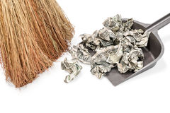 Money sweeps into the garbage dump. Broom sweep crumpled dollars in a dustbin isolated on a white background Royalty Free Stock Photo