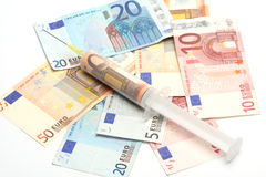 Money and syringe. Money in a syringe - euro banknotes stock image