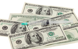 Money and syringe against white Stock Images