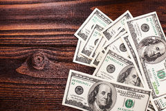 Money on the table. Money american hundred dollar bills carelessly scattered on the wooden table Stock Photography