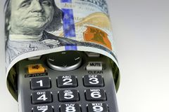 Money talks concept image. Digital cordless phone with US currency one hundred dollar bill Royalty Free Stock Photo