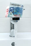 Money on the tap and flowing water. Euro money on the tap and flowing water Royalty Free Stock Photography
