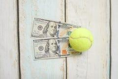Money and tennis balls. On wooden floor Stock Photo