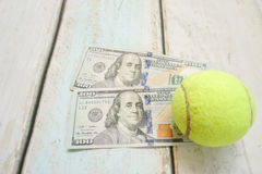 Money and tennis balls Royalty Free Stock Images