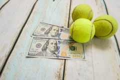 Money and tennis balls. On wooden floor Royalty Free Stock Photos