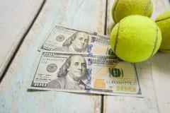 Money and tennis balls. On wooden floor Stock Images