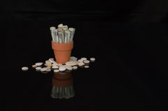 Money in terracotta pot with buttons Royalty Free Stock Image