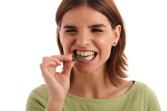 Money testing. Stock photo of a young woman biting silver dollar royalty free stock photo
