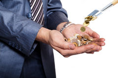 Money are threw to pile of coins by shovel. Businessman cups his hands as he holds a pile of coins. Money are threw to pile of coins by shovel Royalty Free Stock Images