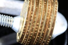 Money is Tight Budget Crisis. US Currency gold coins in a clamp vise on black background Royalty Free Stock Photography