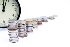 Money and time. Piles of coins arranged in a raw with clock in the background Royalty Free Stock Photos