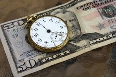 Money and time. Time and money concept image featuring an old pocketwatch and a US fifty dollar bill Stock Photo