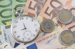 Money and time. Euro bank- notes and clock close-up Royalty Free Stock Images