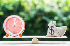 Money and Time balance, Change money into cash or reverse concep. T : US Dollar in sack bag, Clock put on scales on wooden table with nature background. Time stock image