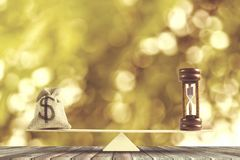 Money and Time balance, Change money into cash or reverse concep. T : US Dollar in sack bag, Hourglass put on scales on wood table with Golden bokeh as Royalty Free Illustration