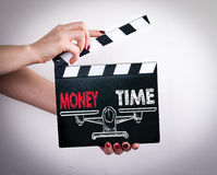 Money and Time Balance. Female hands holding movie clapper.  royalty free stock photo