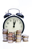 Money and time concept. Pile of coins arranged in front of a clock Stock Photo