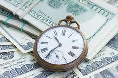 Money and time. Concept - antique pocket watch on pile of american dollars stock photography