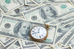 Money and time. Concept - old pocket watch on pile of american 100 bill dollars royalty free stock photos