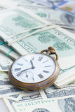Money and time. Concept - old pocket watch on pile of american dollars royalty free stock images