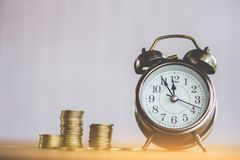 Money and time concept with stack of coin and clock on table. Saving money Royalty Free Stock Photos