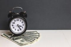 money time Kontanta dollar Retro ringklocka och kassapengar på tabellen Royaltyfria Bilder