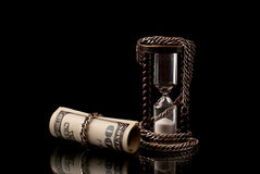 Money and time. U.S>Dollars chained with hourglass with silver chaih. Black background. Studio shot Stock Images