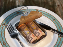 Money in a tin can. A tin can with money on a plate with silverware, placed an old wooden table Stock Image