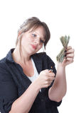 Money to burn. Woman ready to light a stack of money on file; isolated on a white background Royalty Free Stock Photos