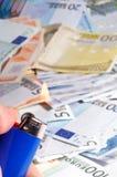 Money to burn. Lighter is burning money - the danger of losing money Stock Image