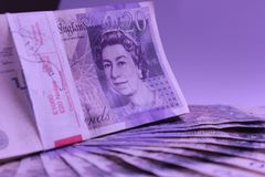 Money to spend 1000pounds roll on the table income travel. English pounds money cash payments pay earn currency 20pounds income tourism scads roll needfull purse Stock Image