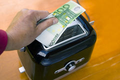 Money In Toaster. Hand roasting a hundred euro banknote in toaster, concept of life expenses Stock Photos