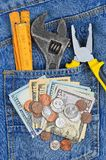 Money and tool in jeans pocket Royalty Free Stock Photo