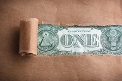 Money through torn paper Royalty Free Stock Image