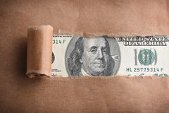 Money through torn paper Royalty Free Stock Images