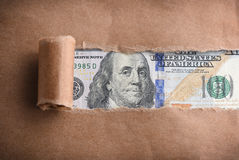 Money through torn paper Royalty Free Stock Photography
