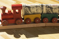 The Money Train. A toy train pulling a cargo of money  This picture could be a reference to 'money delivery', gravy train, cargo, freight.  Also, money supply Stock Photos