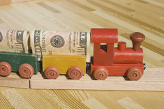 The Money Train. A toy train pulling a cargo of money  This picture could be a reference to 'money delivery', gravy train, cargo, freight.  Also, money supply Royalty Free Stock Photos