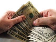 Money transfer from one hand to another. A few bills being transfered from one person to another Stock Photo