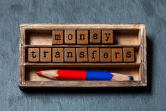 Money transfers concept. Vintage box, wooden cubes phrase with old style letters, red blue colored pencil. Gray stone Royalty Free Stock Photos