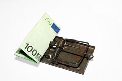 Money trap. Photo of a Mouse Trap With a Roll of Money as Bait Stock Image