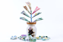 Money tree. Money growing from a vase and falling to the ground Stock Photography