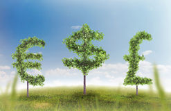 Money trees. Financial growth and success on a green summer natural green grass landscape with a single trees in the shape of a money sign showing a business Royalty Free Stock Photo